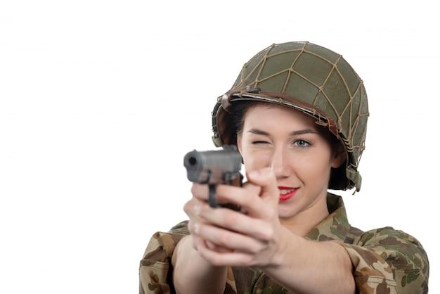 De vrij jonge vrouw kleedde zich in ww2 amerikaanse militaire eenvormig met helm en pistool