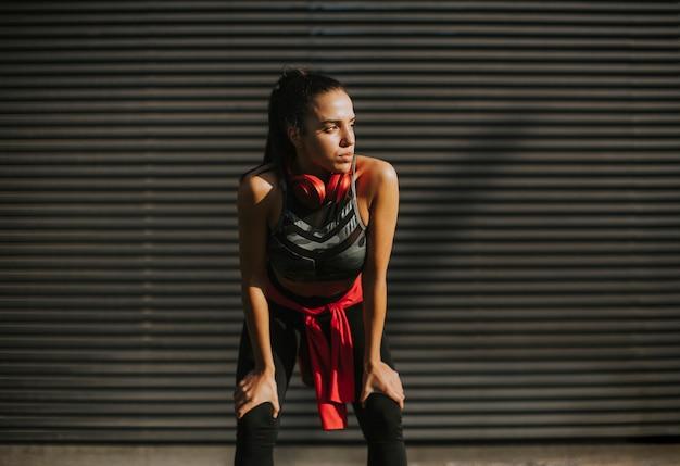 De vrij jonge vrouw neemt een pauze na het lopen in stedelijk gebied