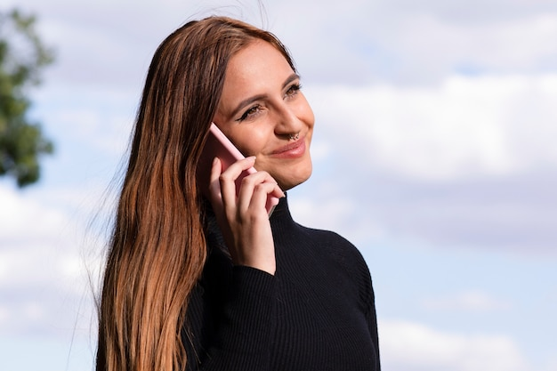 De vrij jonge vrouw spreekt met haar telefoon in openlucht glimlachend