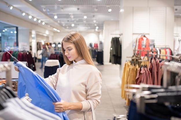 De vrij jonge vrouwelijke klant die zich door rek met nieuwe overhemden bevindt en blauwe in haar bekijkt dient vrijetijdskledingafdeling in