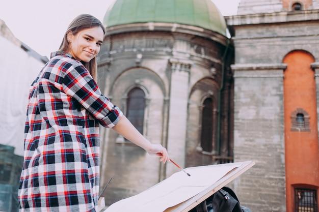 De vrij jonge vrouwenkunstenaar schildert oude architectuur in de stad.