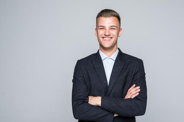 De vrij jonge zakenman van de mensenstudent in jasje houdt zijn wapens gekruist geïsoleerd op lichtgrijze muur