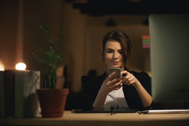 De vrij jonge zitting die van de vrouwenontwerper binnen telefonisch babbelen
