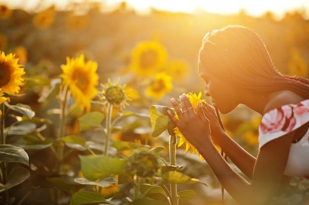 De vrij jonge zwarte die zomerjurk draagt stelt in een zonnebloemveld.