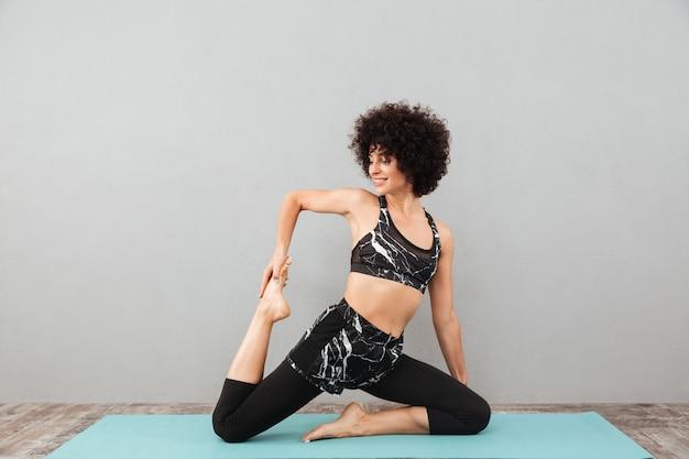 De vrij krullende fitness vrouw maakt sportyoga oefeningen