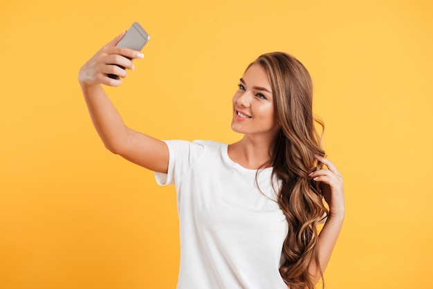 De vrij leuke mooie jonge vrouw maakt selfie door mobiele telefoon