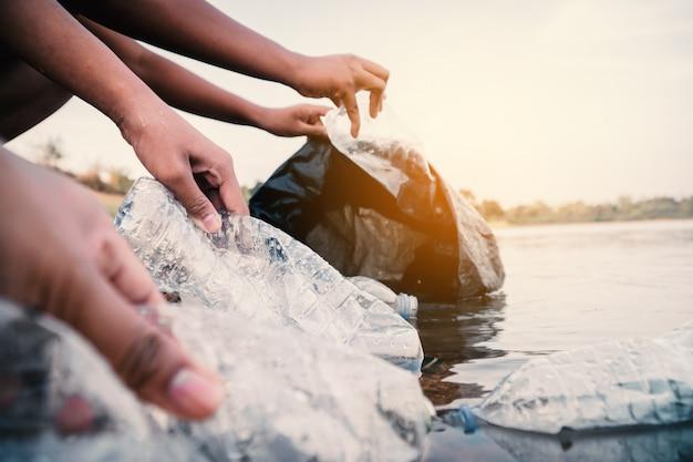 De vrijwilliger haalt een plastic flesje in de rivier op en beschermt het milieu tegen een vervuilingsconcept.