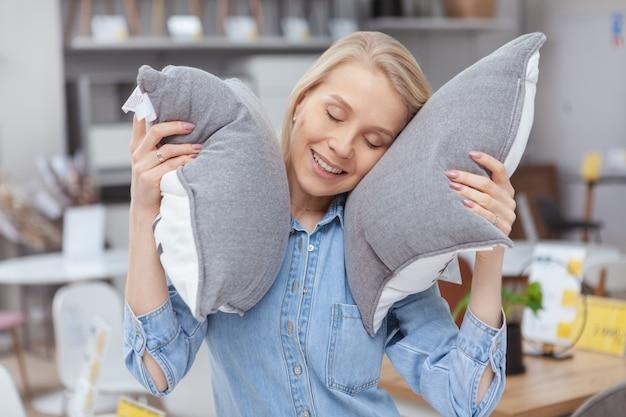 De vrolijke aantrekkelijke vrouw die met haar ogen glimlachen sloot, leggend haar hoofd op een hoofdkussen, winkelend bij het inrichten van opslag