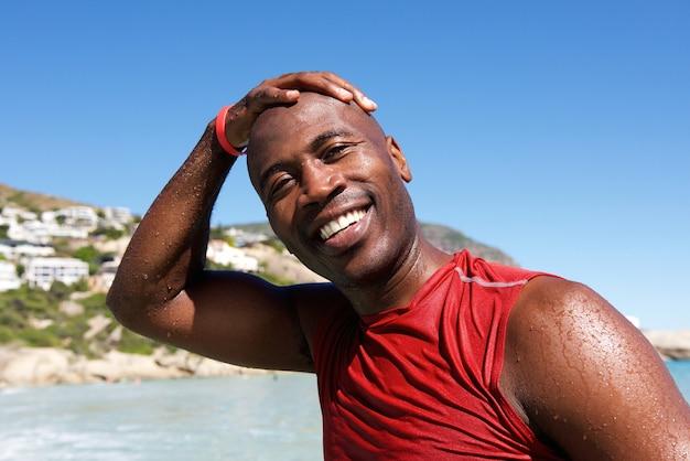 De vrolijke afro afrikaanse kerel bij het strand na zwemt