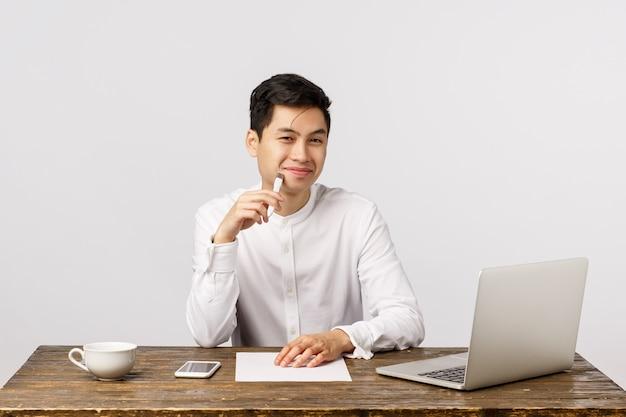 De vrolijke aziatische mannelijke ondernemer in bureau, zit werkend bureau, tevreden glimlachen, raakt lippen met pen zoals opgestelde interessante gedachte, heeft plan in gedachten, rapport voorbereiden