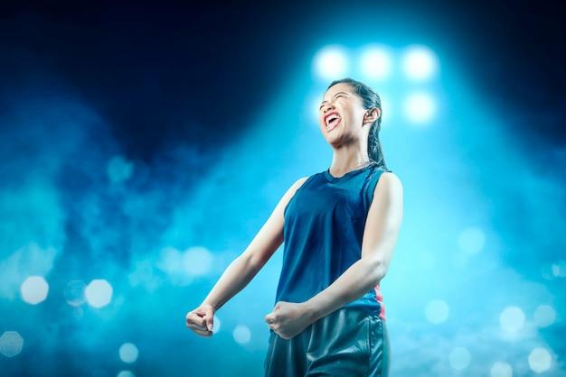 De vrolijke aziatische speler van het meisjesbasketbal in blauwe sportkleding met gelukuitdrukking in het basketbalhof