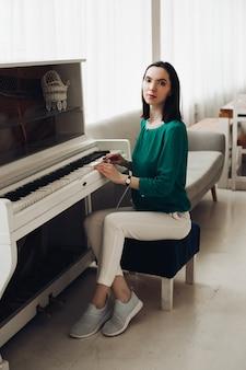 De vrolijke dame zit op de stoel dichtbij de witte pianoglimlachen