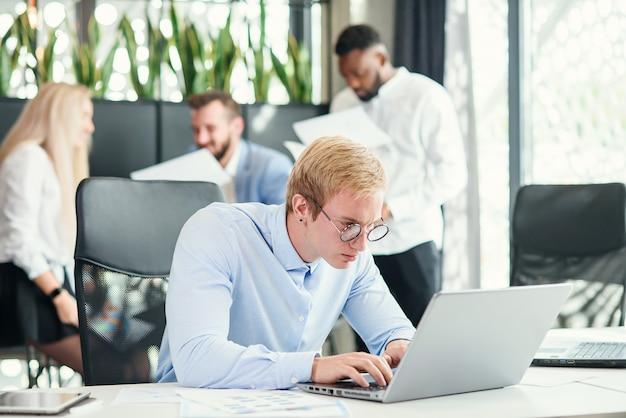 De vrolijke doelgerichte mannelijke beambte met grappige oogglazen zit op zijn werkplaats en gebruikt laptop om financiële taken op te lossen.