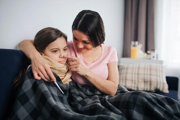De vrolijke en positieve jonge moeder omhelst en troost haar kind. ze raakt de punt van haar neus. ziek klein meisje kijk en zit stil. ze bedekt met deken.