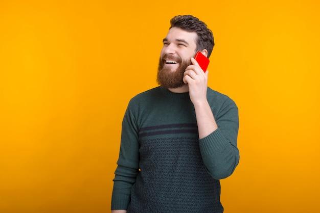De vrolijke gebaarde mens spreekt op de telefoon en glimlacht op gele ruimte.