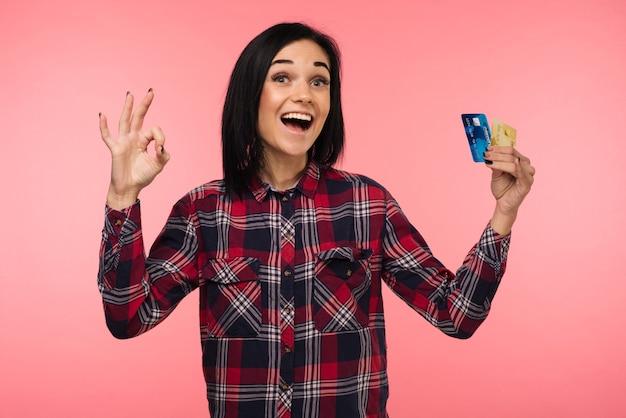 De vrolijke gelukkige verraste jonge vrouw met creditcard die zingen ok over roze achtergrond tonen