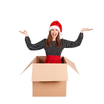 De vrolijke gelukkige vrouw in kleding en kerstmishoed die pret hebben terwijl het zitten in de grote giftdoos en heft zijn handen omhoog van geluk op. geïsoleerd