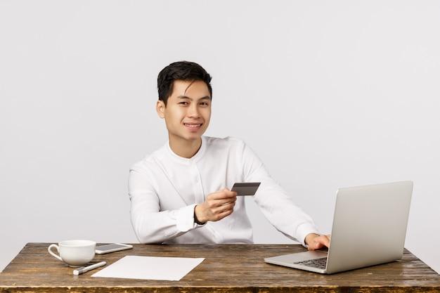 De vrolijke glimlachende aziatische jonge creditcard van de ondernemersholding en het gebruiken van laptop