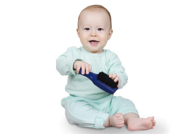 De vrolijke glimlachende baby zit geïsoleerd op wit oppervlak