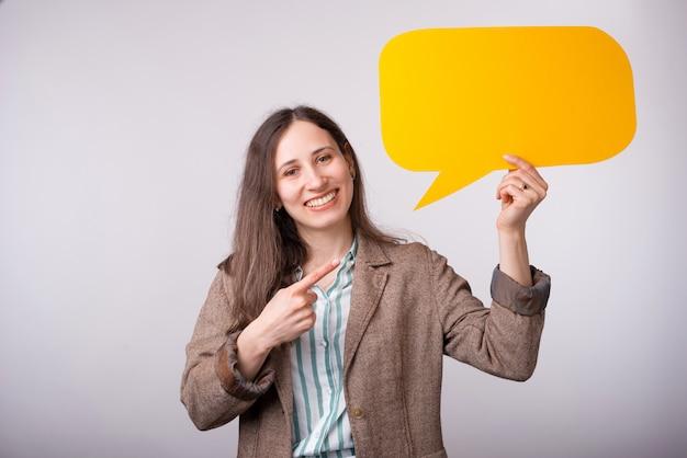 De vrolijke glimlachende jonge vrouw houdt een gele bellentoespraak op wit