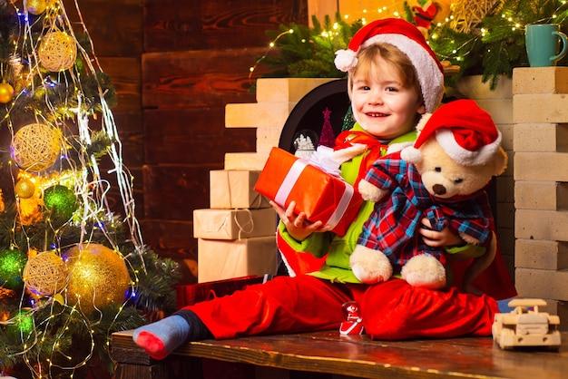 De vrolijke glimlachende jongen die van de babysanta zijn teddybeer en kerstcadeau dichtbij open haard houdt en