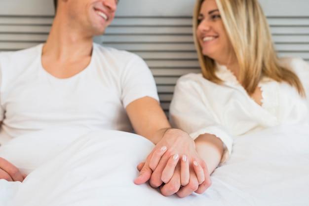 De vrolijke hand van de mensenholding van jonge vrouw in bed