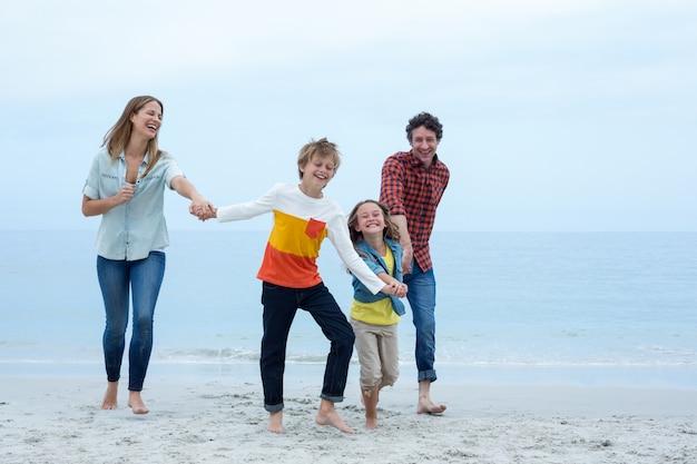 De vrolijke handen van de familieholding terwijl het lopen op zee kust
