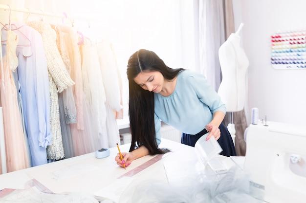 De vrolijke indische naaister die dichtbij het naaien van hulpmiddelen zit, trekt het ontwerp van kleding met een patroon in haar eigen workshop uit