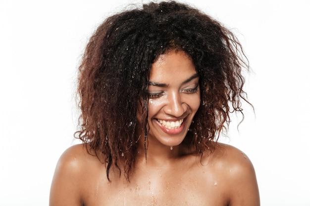 De vrolijke jonge afrikaanse vrouw maakt haar gezicht schoon met water.