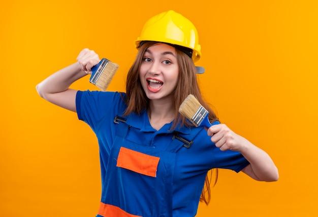 De vrolijke jonge arbeider van de vrouwenbouwer in eenvormige bouw en de verfborstels van de veiligheidshelm die breed glimlachen