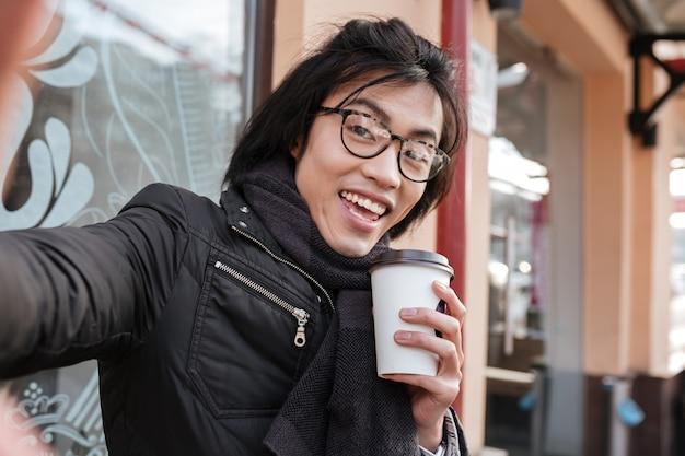 De vrolijke jonge aziatische mens het drinken koffie en maakt selfie.