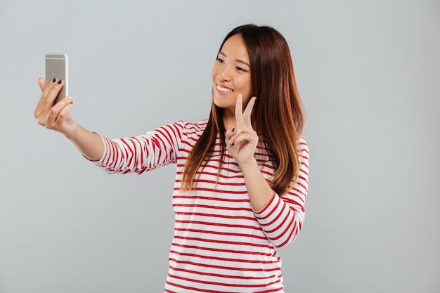 De vrolijke jonge aziatische vrouw maakt selfie telefonisch