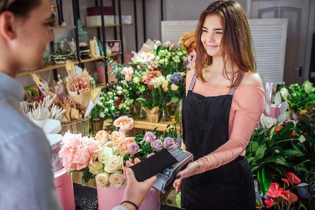 De vrolijke jonge bloemist houdt therminal geld in handen. ze kijkt naar de klant. de jonge telefoon van de zakenmangreep boven therminal. hij betaalt voor bloemen.