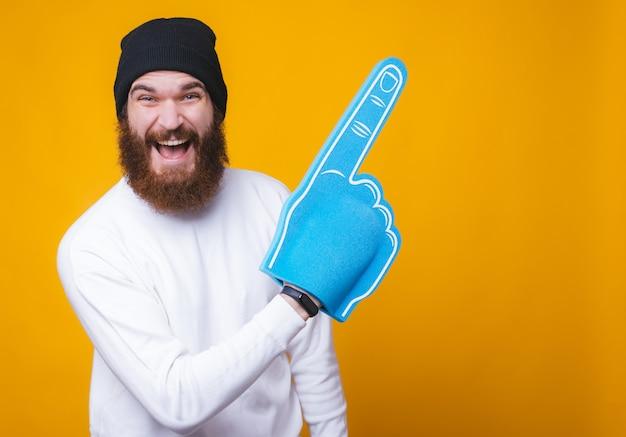 De vrolijke jonge gebaarde mens lacht en richt op een exemplaarruimte met een grote ventilatorhandschoen op gele muur.