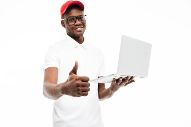 De vrolijke jonge mens die glb dragen maakt duimen op gebaar
