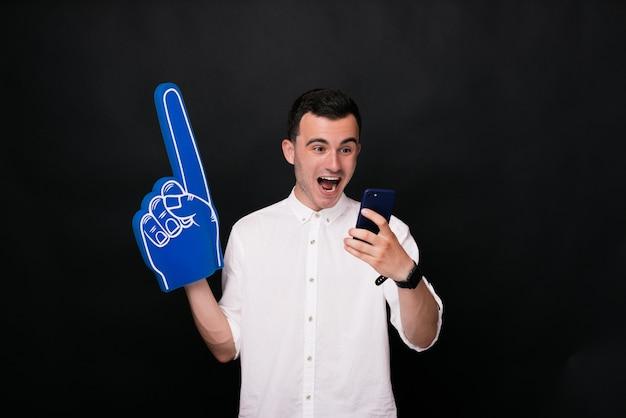 De vrolijke jonge mens in wit overhemd houdt schuimhandschoen en een telefoon op zwarte achtergrond.