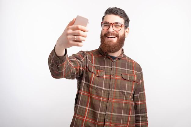 De vrolijke jonge mens maakt een selfie met zijn telefoon op witte achtergrond.