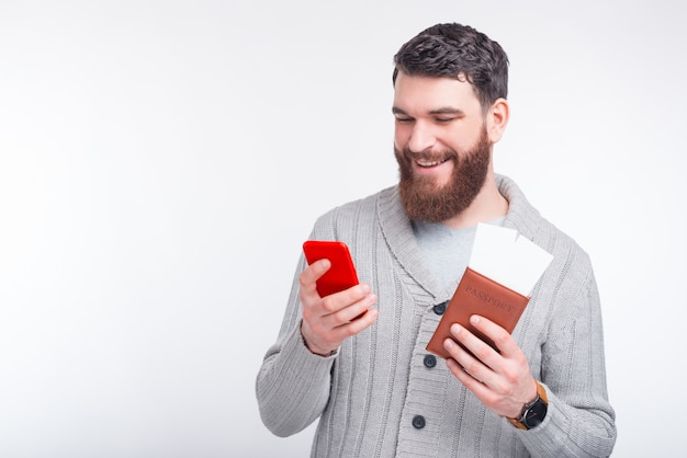 De vrolijke jonge mens maakt online inchecken op zijn telefoon en houdt zijn paspoort met twee kaartjes