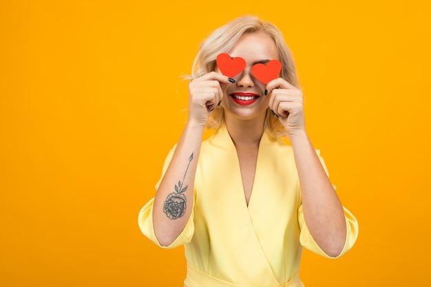De vrolijke jonge vrouw met kort blonde haar glimlacht en houdt twee kleine harten die op sinaasappel worden geïsoleerd