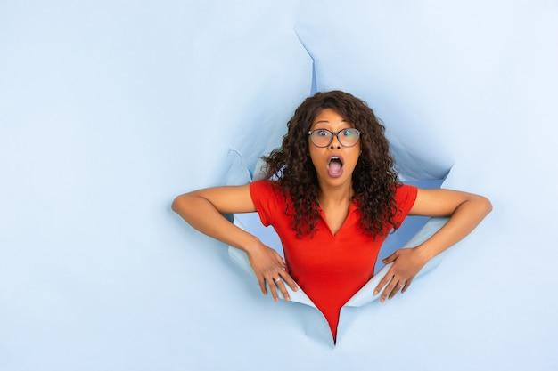 De vrolijke jonge vrouw stelt op gescheurde blauwe document gatenachtergrond, emotioneel en expressief