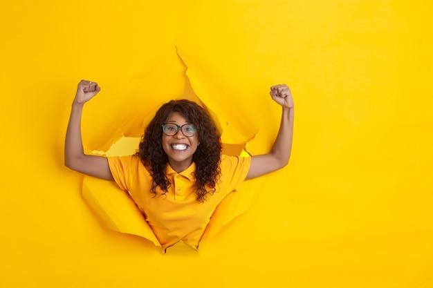 De vrolijke jonge vrouw stelt op gescheurde gele document gatenachtergrond, emotioneel en expressief