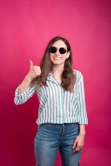 De vrolijke jonge vrouw toont als of duim op gebaar