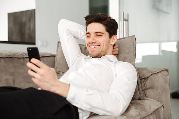 De vrolijke jonge zakenman in huis ligt op bank