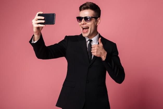 De vrolijke jonge zakenman maakt selfie met omhoog duimen telefonisch.