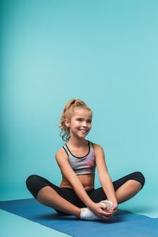 De vrolijke jonge zitting van het sportenmeisje op een geschiktheidsmat die yogaoefeningen doet die over blauwe muur worden geïsoleerd