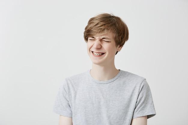 De vrolijke kaukasische jonge mens grijnst, heeft dolblije uitdrukking, klemt tanden met steunen vast, blij zijnd. het glimlachende blonde modieuze mannetje in grijs t-shirt drukt positiviteit uit