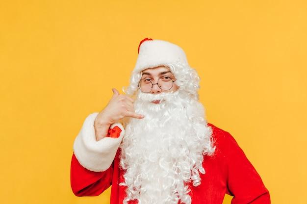 De vrolijke kerstman imiteert een bel me-gebaar
