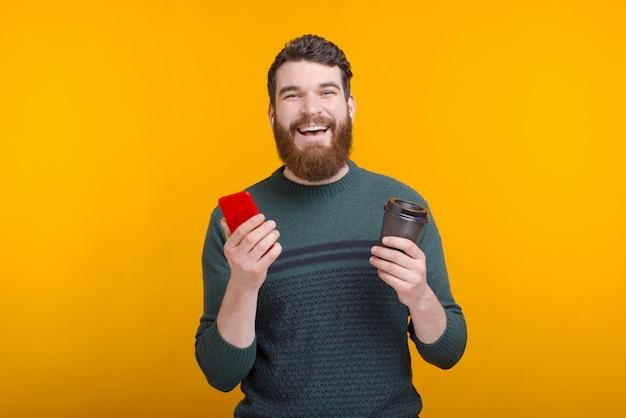 De vrolijke mens houdt een document kop en zijn telefoon op gele achtergrond.