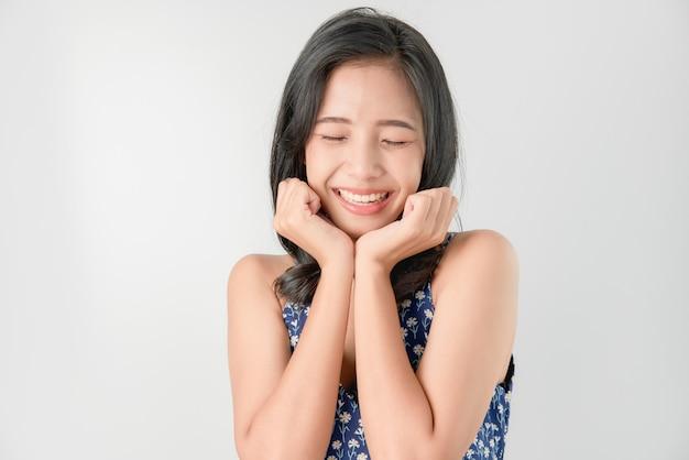 De vrolijke mooie aziatische glimlach van het vrouwen gelukkige gezicht op grijs.