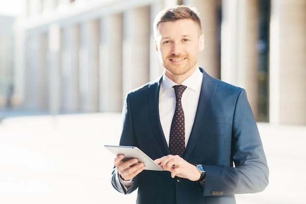De vrolijke succesvolle jonge mannelijke uitvoerende manager, draagt formele kleding, controleert e-maildoos op modern touchpad